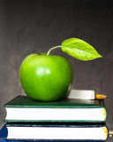 Apple, chalk and pencil on textbooks Stock Photo