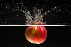 Apple che cade in acqua Immagini Stock