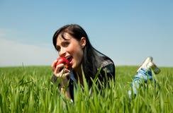 Apple che mangia ragazza su erba verde Fotografia Stock Libera da Diritti