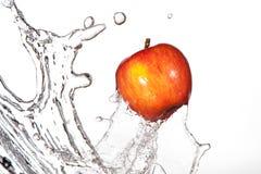 Apple che spruzza attraverso l'acqua Fotografia Stock Libera da Diritti