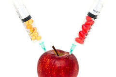Apple with chemicals. Juicy red apple and syringes with vitamins and chemicals Stock Photos