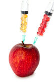 Apple with chemicals. Juicy red apple and syringes with vitamins and chemicals Stock Images
