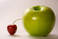 Apple and cherry. Contrast of small and big, contrast of red and green Stock Photo