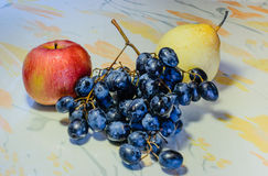 Apple, Chinese pear and bunch of grapes. In the frame - the gifts of nature. Autumn harvest: Apple with water droplets on red, bulk sides, bunch of black grapes Royalty Free Stock Photography