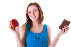 An apple or chocolate?. An apple and chocolate bar choice of young beautiful brunette Stock Photo