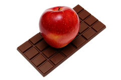 Apple on chocolate. Eternal question of the person: is useful or tasty food? To choose an apple or chocolate Royalty Free Stock Photos