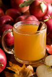 Apple cider. A cup of hot apple cider surrounded by red apples Stock Photo