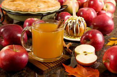 Apple cider. A cup of hot apple cider, caramel apple and apple pie surrounded by fresh fruits Stock Image