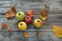 Apple cider in  bottle,  and fresh apples on wooden background Royalty Free Stock Photography