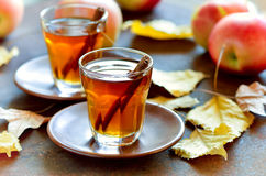 Apple cider. With cinnamon sticks in glasses decorated with autumn yellow leaves Royalty Free Stock Image