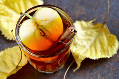 Apple cider. With cinnamon sticks in glasses decorated with autumn yellow leaves Stock Photos