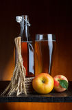 Apple cider glass and bottle. With apples and wheat still life Stock Image