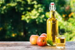 Apple cider in glass bottle. Apple cider in glass and in bottle with fresh apples on wooden table with blurred natural background. Copy space. Summer drink stock photos