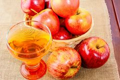 Apple cider glass and red apples. In the rustic wicker basket on wooden background Royalty Free Stock Images