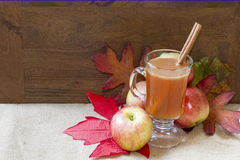 Apple Cider. Hot Apple Cider with apples and fall leaves on burlap with wood background Stock Photography
