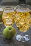 Apple cider with ice cubes. Glass of cold refreshing apple cider with ice cubes on and apples wooden table Royalty Free Stock Photo