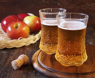 Apple cider and red apples. Two cups of Apple Cider and red apples in wicker basket Royalty Free Stock Images