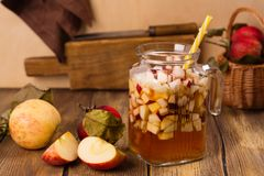 Apple cider sangria in a glass jar on wooden table Royalty Free Stock Photography