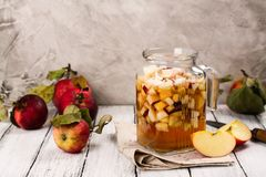 Apple cider sangria in a glass jar on wooden table Royalty Free Stock Photo
