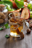 Apple cider with spices in a glass cup, vertical Stock Photo