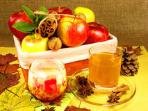 Apple cider still life. Apples basket with cinnamon, and candle with a cup of cider Stock Image