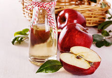 Apple cider vinegar and apples over white wooden background Royalty Free Stock Photo