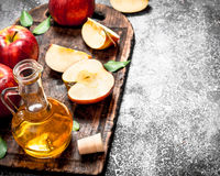 Apple cider vinegar with fresh apples on cutting Board. On rustic background Stock Photos