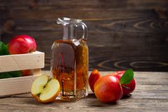Apple cider vinegar and fresh red apple. On a wooden background royalty free stock photos
