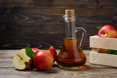 Apple cider vinegar and fresh red apple. On a wooden background royalty free stock photo