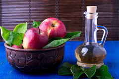 Apple cider vinegar in glass bottle on blue background. Red apples in brown bowl. Apple cider vinegar in glass bottle on blue background. Red apples in brown Royalty Free Stock Image