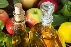 Apple cider vinegar in a glass vessel and apples Royalty Free Stock Photos