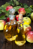 Apple cider vinegar in a glass vessel and apples Stock Photography