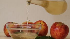 Apple cider vinegar stream falling. Organic apple cider vinegar pouring from the bottle with fruits in the backgroundn stock video footage