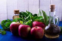 Apple cider vinegar. Three glass bottle on blue background. Red apples Stock Photos
