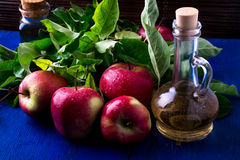 Apple cider vinegar. Three glass bottle on blue background. Red apples Royalty Free Stock Photos