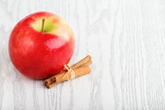 Apple and cinnamon. One red apple white the cinnamon royalty free stock images