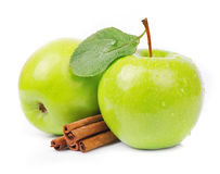 Apple with cinnamon. Sweet green apple with cinnamon rods on white stock photo