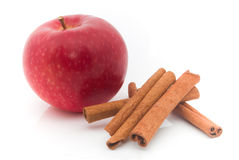 Apple and cinnamon. Red apple and cinnamon on white background royalty free stock photos