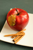 Apple with cinnamon and autumn leaves. Red apple with cinnamon and autumn leaves on a white plate Stock Photography
