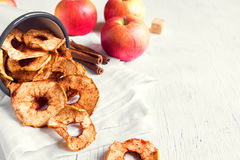 Apple cinnamon chips. Organic apple cinnamon chips slices in metal mug over white background with copy space - healthy vegan vegetarian fruit snack or ingredient stock photos