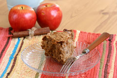 Apple Cinnamon Coffee Cake. Apple coffee cake slice on a plate with a fork with cinnamon sticks and apples in the background Royalty Free Stock Images