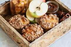 Apple cinnamon crumble muffins, salted caramel sauce, spices in. A wooden box. White stone background. Close up and copy space royalty free stock image