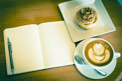 Apple cinnamon roll served with latte art coffee and notebook on Royalty Free Stock Image
