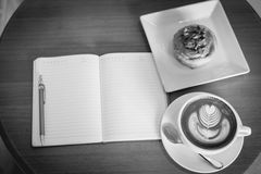Apple cinnamon roll served with latte art coffee and notebook on Royalty Free Stock Photo