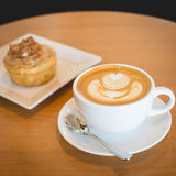 Apple cinnamon roll served with latte coffee on the table at res Royalty Free Stock Photo