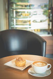 Apple cinnamon roll served with latte coffee on the table at res Stock Photo