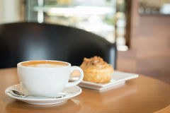 Apple cinnamon roll served with latte coffee on the table at restaurant Stock Photo