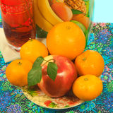 Apple and citrus fruit on a plate, glassful and carton of juice Stock Photo