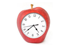 Apple Clock with Time. A bright red apple is isolated on a white background with a clock inside of it ticking. This image can represent a health plan Stock Photography
