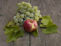 Apple and cluster of grapes with leaves on a wooden table Stock Photography
